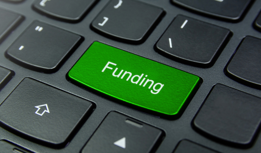 Business Concept: Close-up the Funding button on the keyboard and have Lime, Green color button isolate black keyboard